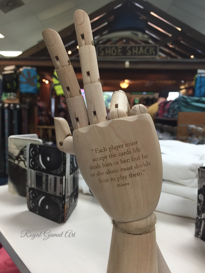 Hand with Voltaire quote at the Shoe Shack.